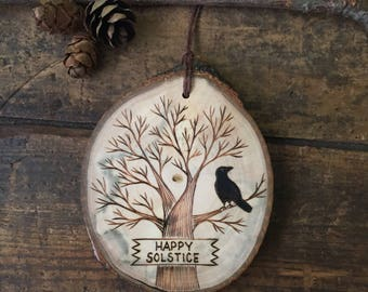 Wood burned Happy Solstice ornament or wall hanging. Available with or without raven.