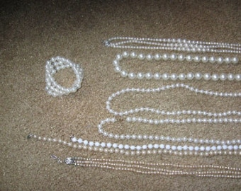A lot of fashion pearl like necklaces and one bracelet.