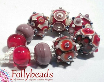 Handmade Lampwork Artisan glass bead set in Ivory, Reds and purples with silver dots.