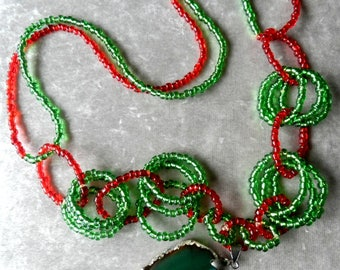 Beautiful long style necklace with a green Agate medallion,with red and green beads