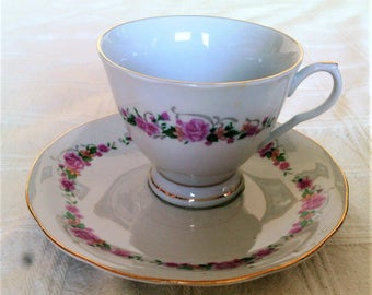 Vintage Footed Porcelain Fine China Cup And Saucer Decorated With A Garland Of Roses