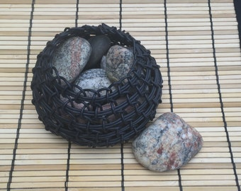 Small handwoven coiled basket made from black coated wire