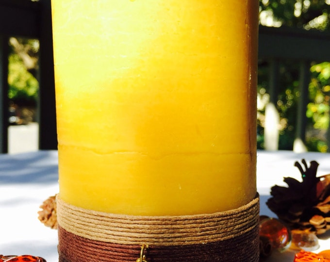 100% Pure Beeswax Pillar Candle wrapped in natural hemp cord and charmed with a golden Honeybee
