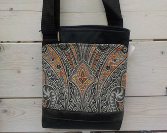 Black nylon handbag with orange tapistry, adjustable shoulder  strap, weatherproof, urban, minimalist.