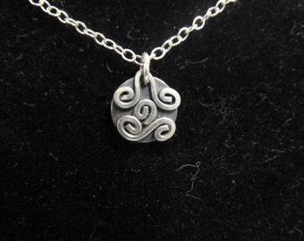 An abstract silver pendant
