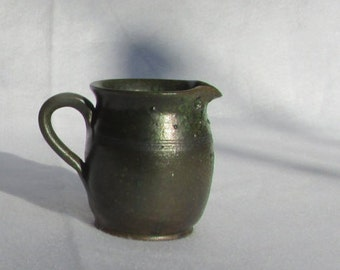 Woodstock small pottery pitcher,  hallmark on bottom, good condition, cute little pitcher would be great with cream, syrup on your table