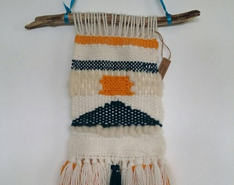 Woven wall hanging in wool, wool Wick, and wood. Home decor.