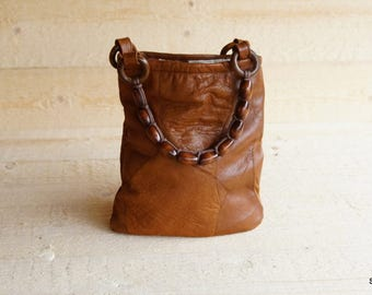 Bag made of recycled leather with straps of wooden beads
