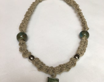 thick knotted hemp with glass accent beads and metal pendant of green fern leaf