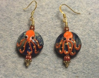 Blue and orange lampwork octopus bead earrings adorned with orange Czech glass melon beads.