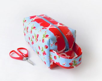 Zippered boxy pouch/make-up/cosmetic pouch with handle, with red strawberries on a light blue background and red clamshell accents