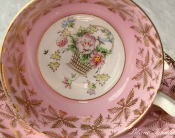 Gladstone, England: Soft pink tea cup and saucer with charming basket of flowers