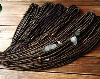 Brown thin dreads with feather beads. Classic dreadlocks
