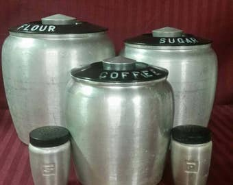 Aluminum canisters, flour, sugar, coffee, salt and pepper.