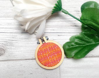 Knitted art framed in a wooden hoop pendant.  orange and pink.  necklace or brooch option.  Statement jewellery for art lover.  unique gift
