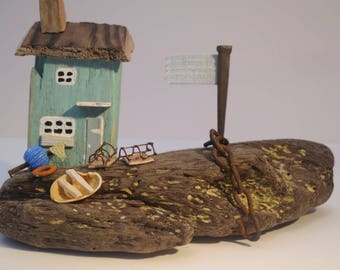 Green driftwood seaside cottage on seasculpted block of driftwood.