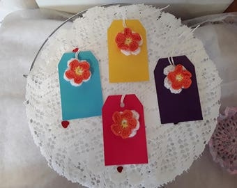 Four cute gift tags; orange and white double crochet cotton flowers attached to coloured tags