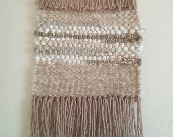 Hand woven wall hanging in neutral color