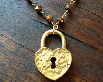 Golden lock necklace on a bronze pyrite rosary chain. A heart shaped lock with open key hole.