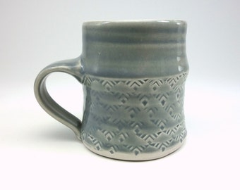 Grey glazed porcelain mug with stamped pattern