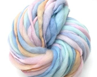 Super bulky handspun yarn, 62 yards and 3.2 ounces/ 91 grams, spun thick and thin in pastel rainbow merino wool