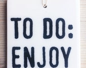 porcelain wall tag screenprinted text to do: enjoy today.