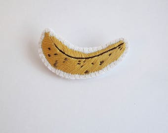 Embroidered banana brooch on cream muslin with cream felt backing yellow and brown cotton thread An Astrid Endeavor kitsch fashion Spring