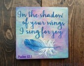 """7""""x7"""" wood sign with Bible verse """"In the shadow of your wings I sing for joy"""" hand painted in a water color style from Psalms 63:7"""