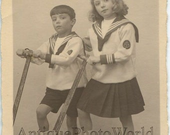 Cute children siblings in sailor suits on scooters antique studio photo