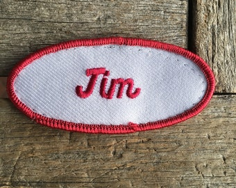 "Jim. An off white work shirt name patch that says ""Jim"" in red script with red border"