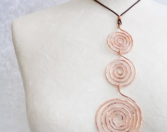 A copper necklace with pendant entirely handmade with pure copper wire with three spirals. A perfect gift to Mother's day