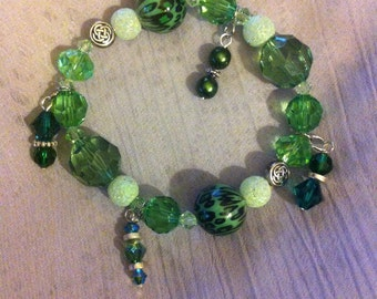 Green mix bead stretch bracelet with Celtic knot beads.