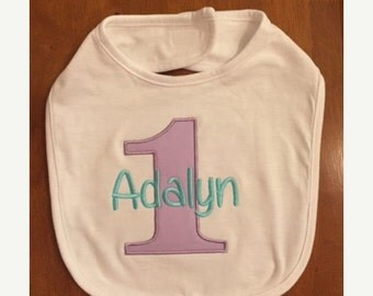 White bib with lavender number 1 and aqua name embroidery