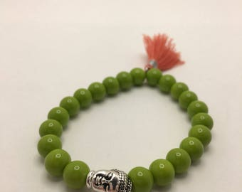 Spring Grass Green Beaded flexible bracelet with a Silver Pewter Buddha Head and Dusty Orange Tassel.