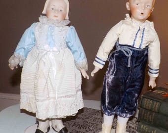 PAIR of vintage (c.1984) Porcelain bisque handmade, jointed dolls. Boy and girl in period | Amish dress on stands for display. Signed.