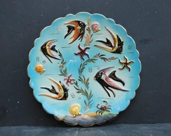 Vintage French 1950s glazed ceramic plate for wall decor. Monaco for Cerdazur, fish decor on blue background. Raised decor, gilt edging.