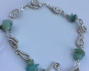Wire wrapped, coiled silver plated bracelet with Aquamarine chips.