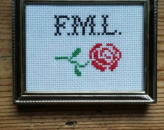 F.M.L. Cross stitch with flower.