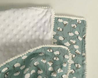 Blue, grey, and white cotton bulb blanket trimmed in white pompoms