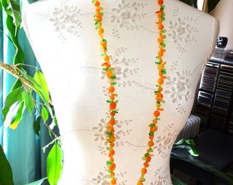 Orange and Green Fruit Salad Necklace. Kitschy orange slices and green leaves in a zany plastic beaded necklace.