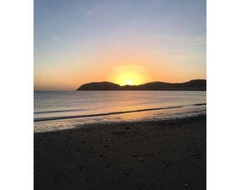 Photograph of A sunrise over llandudno beach in Wales. Ocean view in portrait. minimalist beach photo. Beach sunrise image in wales uk