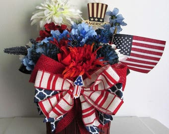 "Patriotic Themed Silk Flower Basket Arrangement, featuring an American Flag, a metal ""America"" Pick, and a Handmade Bow"