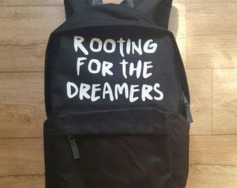 "Black Backpack. ""Rooting for the dreamers"". Also check houseofaudacious.com for more items."