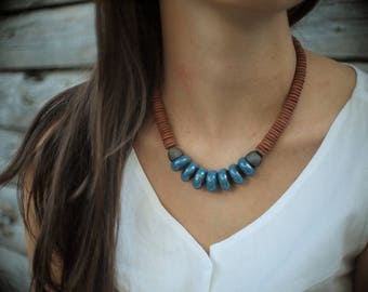 Artisan ceramic necklace with glazed blue and unglazed terracotta flat beads.
