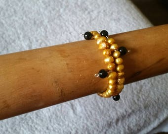 Bracelet made with gold rice pearls and black beads on memory wire
