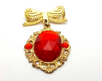 Gold Tone Bow with Framed Plastic Ruby Pendant Brooch Vintage from the 80s Emblem Symbol Runway Statement Jewelry Gift for mother Ribbon