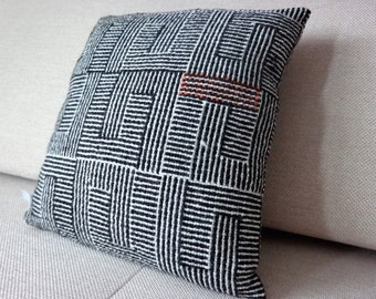 black and white sofa cushion with a blur of orange