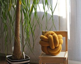 Dark yellow knot cushion