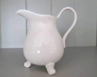 Tiny three footed vintage cream coloured jug.