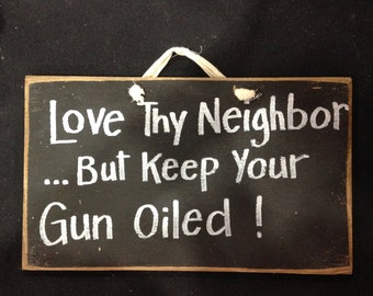 Love thy neighbor but keep your gun oiled sign funny no trespassing plaque yard fence tree porch